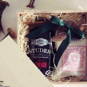 Eine Schweizer Geschenk-Box mit dem Studer Swiss Highland sloe Gin und einem Kräuterkissen von Desirée Rutz.