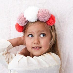 """Dieses trendige Haarband krönt jedes Mädchen-Haupt mit 5 flauschigen Pompons. Für Party oder zum Verkleiden, mit dieser """"Krone"""" strahlt die Trägerin wie eine Königin."""